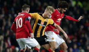 Cambridge United's McGeehan is challenged by Manchester United's Rooney and Fellaini during their FA Cup fourth round soccer match at Old Trafford in Manchester
